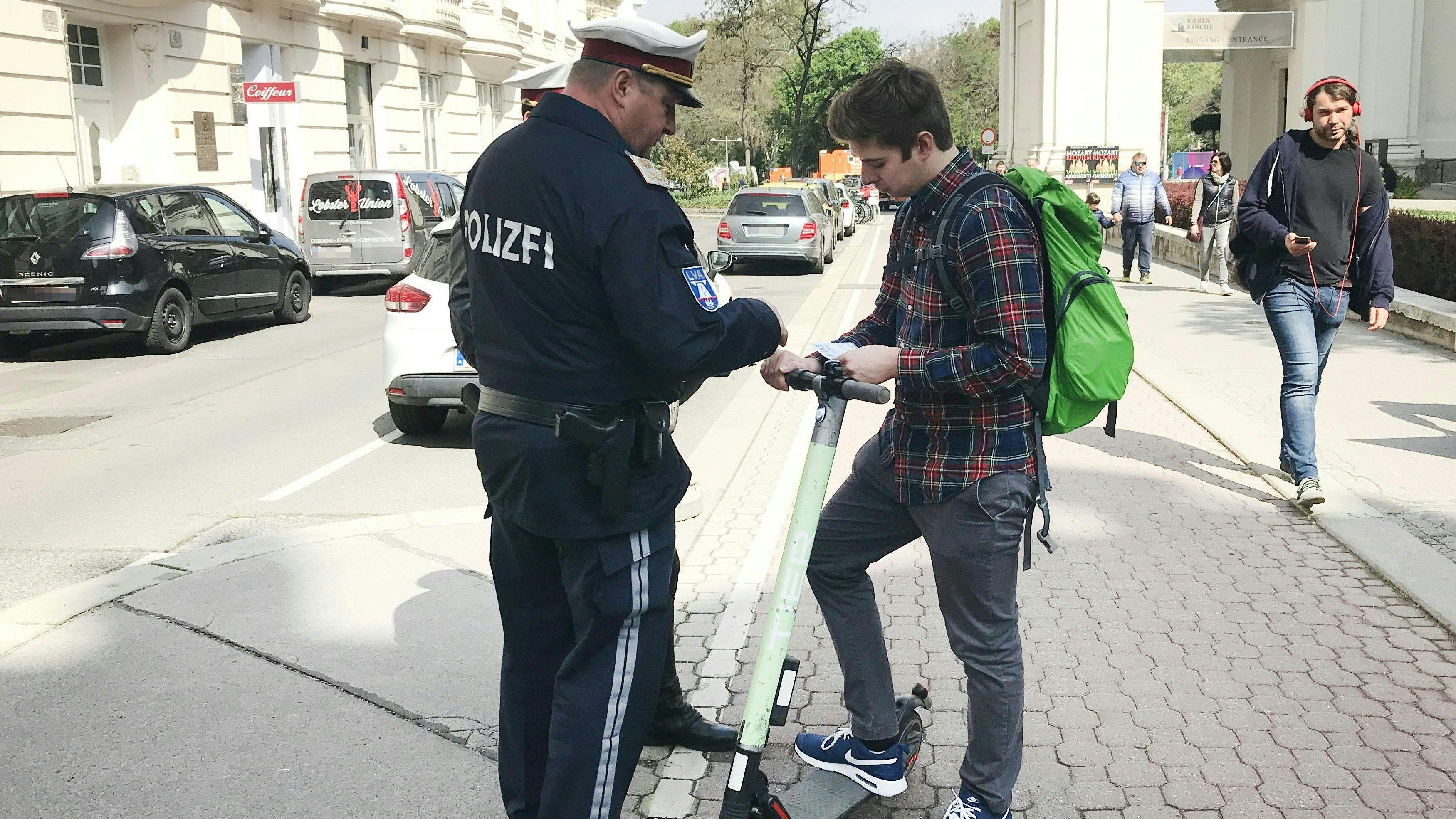 Österreich: Zwei Polizisten kontrollieren einen E-Tretroller-Fahrer