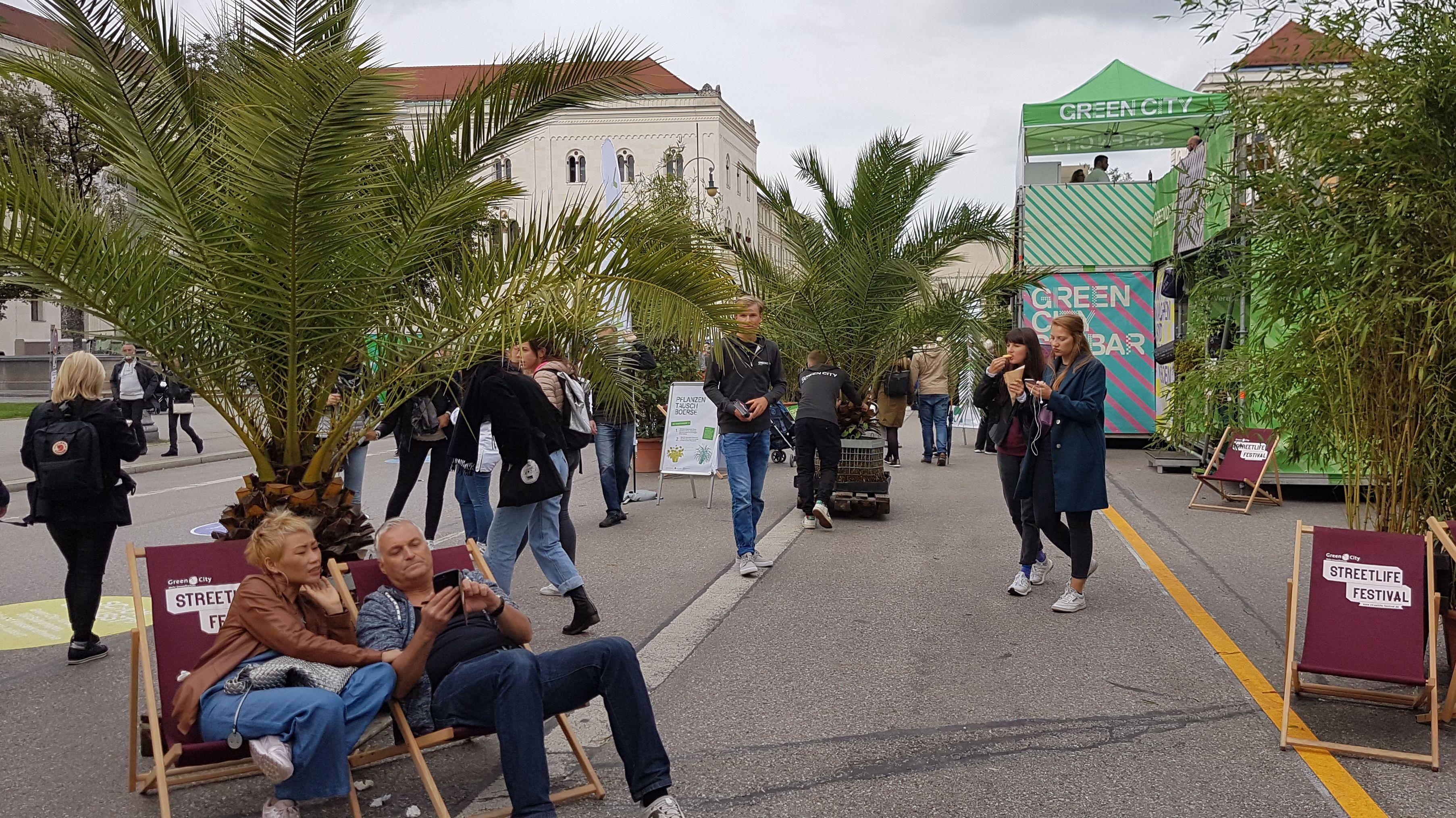 Menschen flanieren und sitzen auf der für den Verkehr gesperrten Münchner Ludwigstraße.