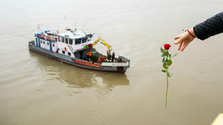 Eine Frau wirft eine Blume von der Margaretenbrücke aus in die Donau