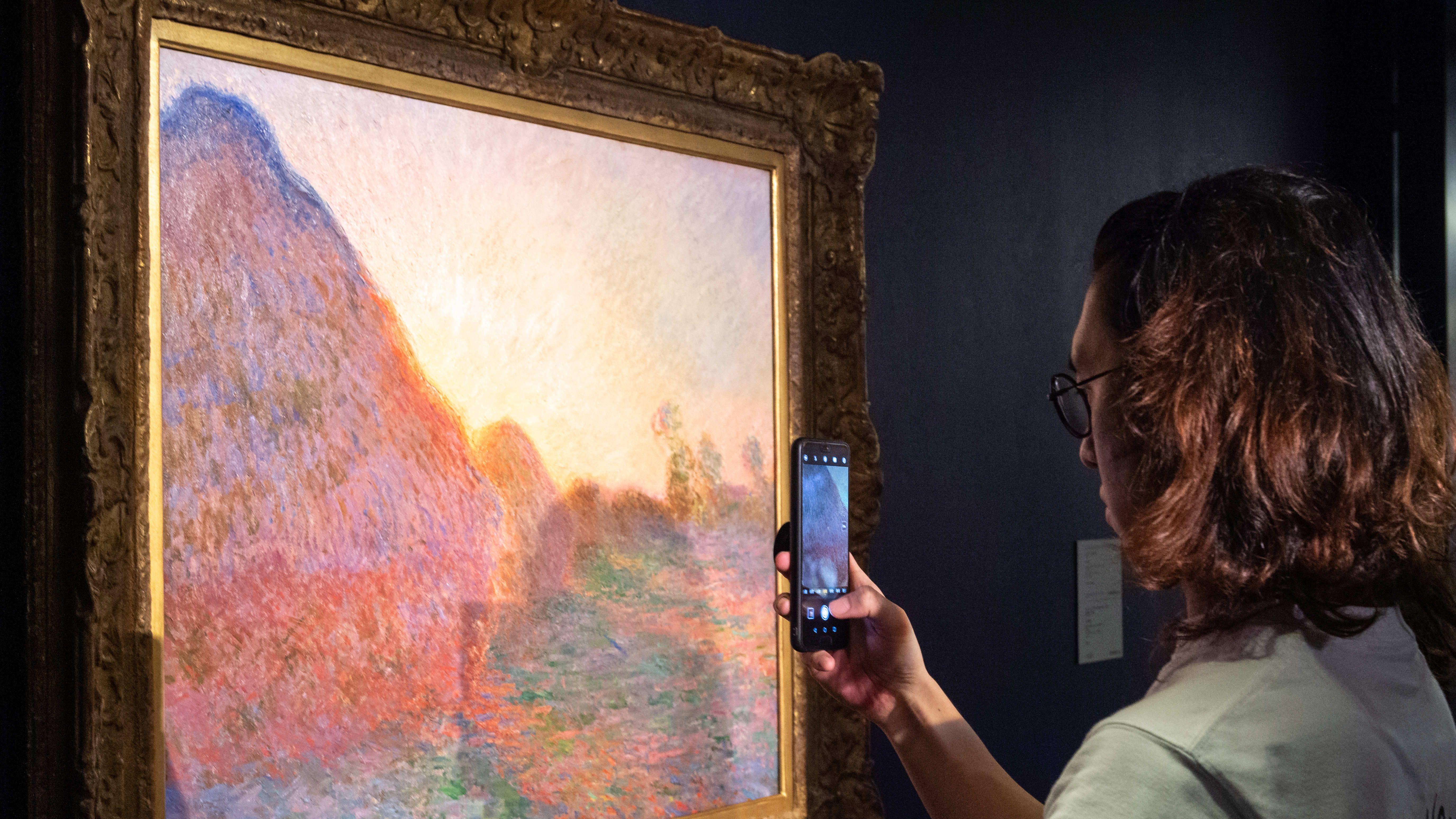 """Ein Museumsbesucher macht mit dem Smartphone ein Foto von Claude Monets Gemälde """"Meules"""""""