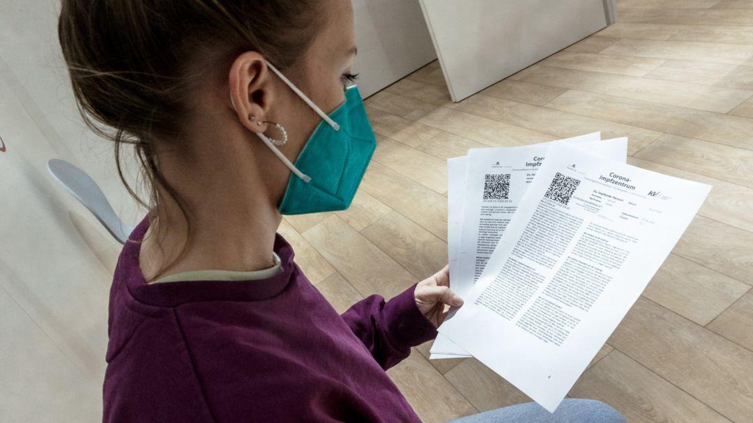 Eine junge Frau liest Informationsblätter zur Impfung