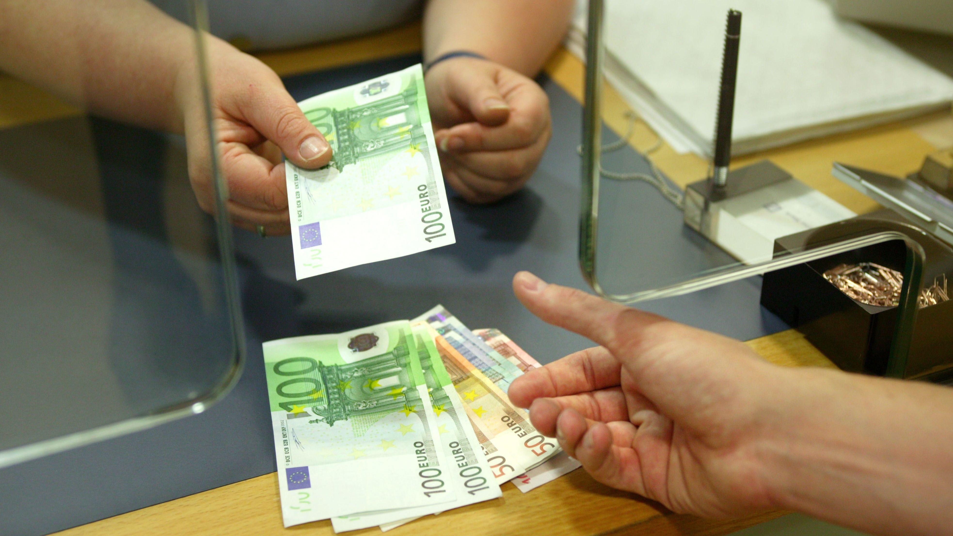An einem Schalter bekommt ein Bankkunde Geld ausgezahlt.