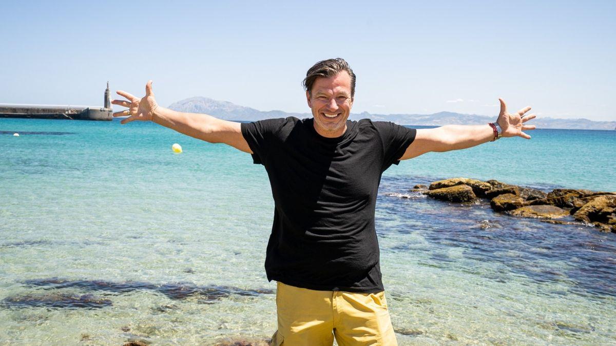 André Wiersig steht am Meer und breitet lachend die Arme aus.