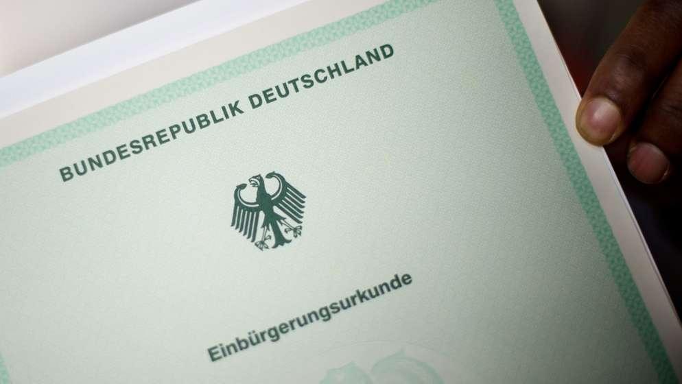 EinMann hält eine Einbürgerungsurkunde in der Hand. | Bild:dpa/ Julian Stratenschulte