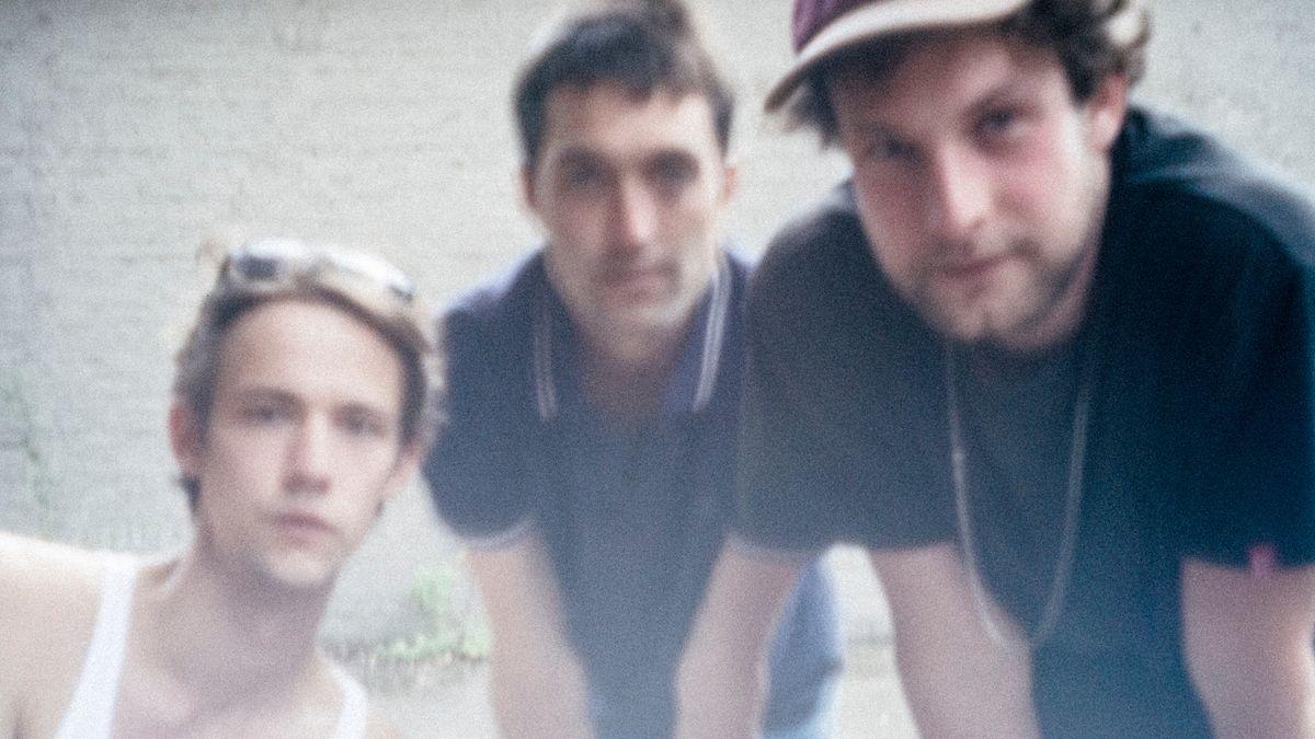 Christopher Annen, Henning May und Severin Kantereit blicken auf einem unscharfen Foto mit blassen Farben in die Kamera