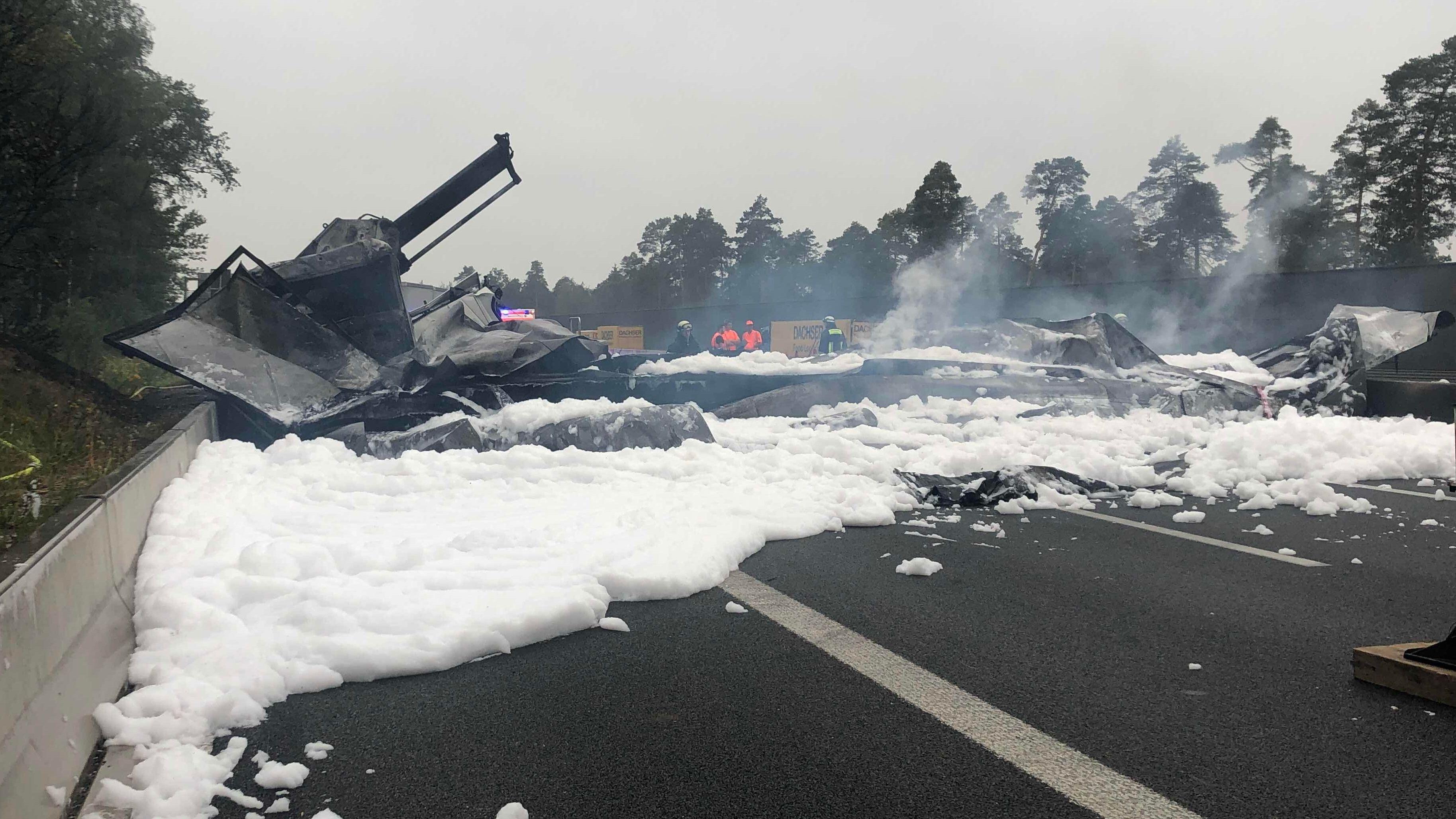 Rauchende Trümmerteile von Lkw und Löschschaum auf der Autobahn verteilt