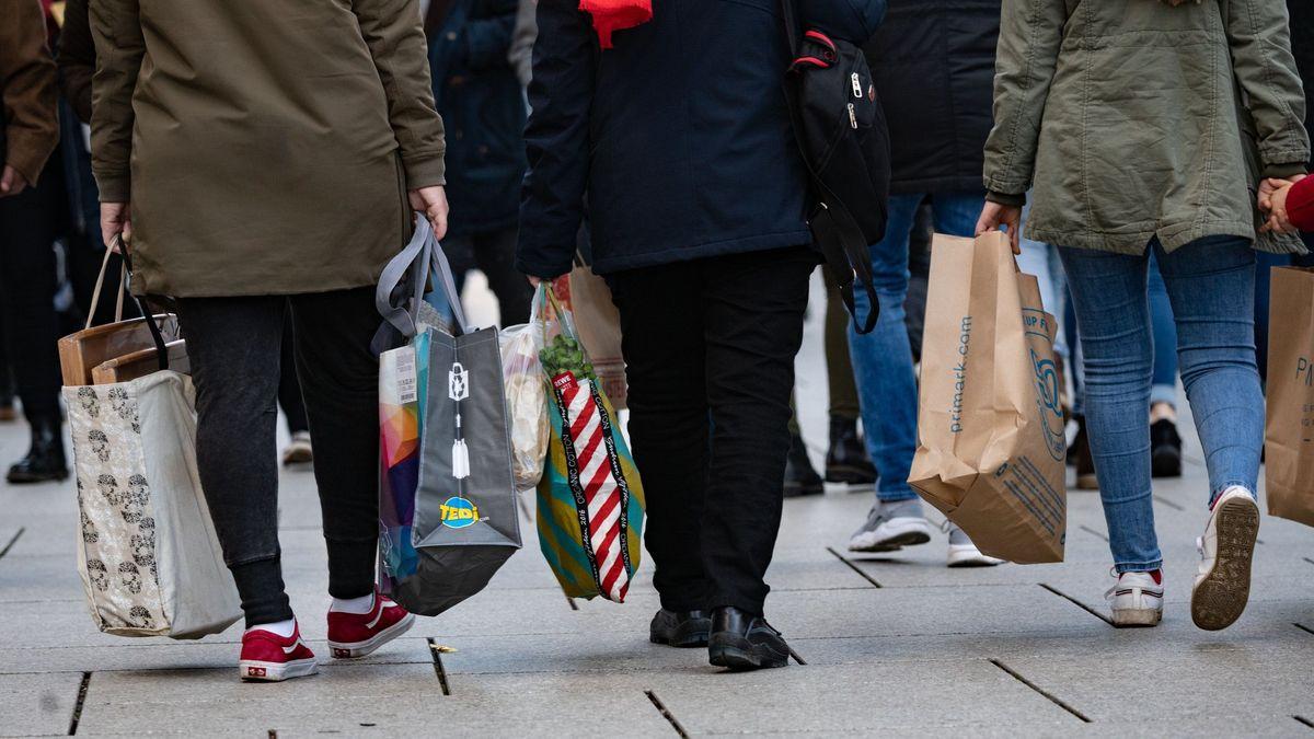 Leute laufen mit Einkaufstaschen durch die Fußgängerzone
