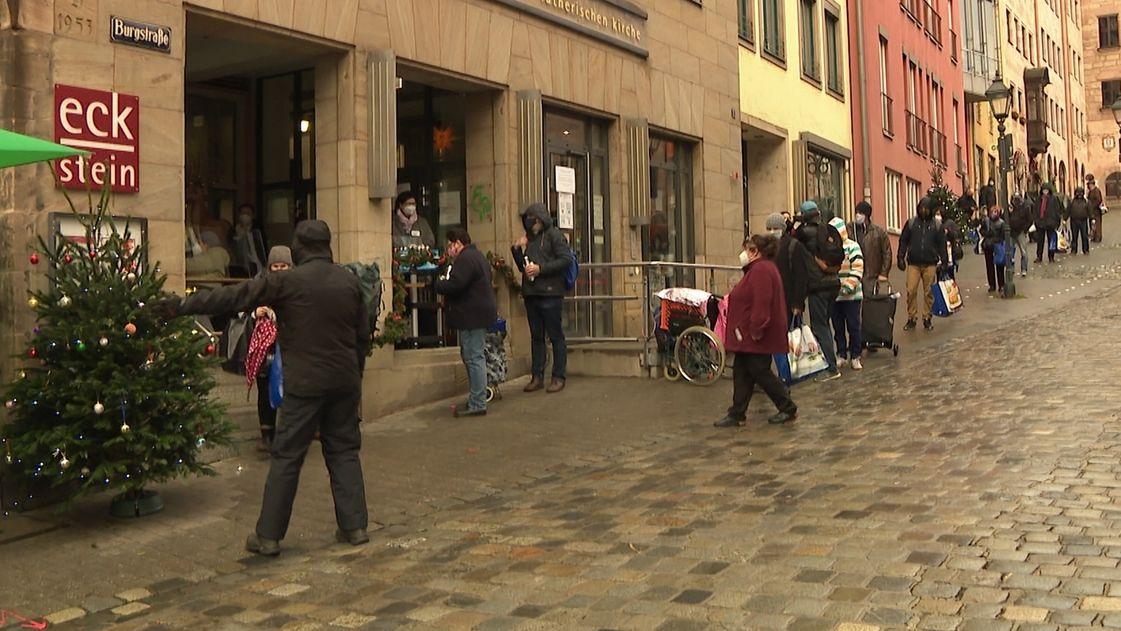 Menschen stehen bei der Obdachlosenweihnacht in der Nürnberger Innenstadt an