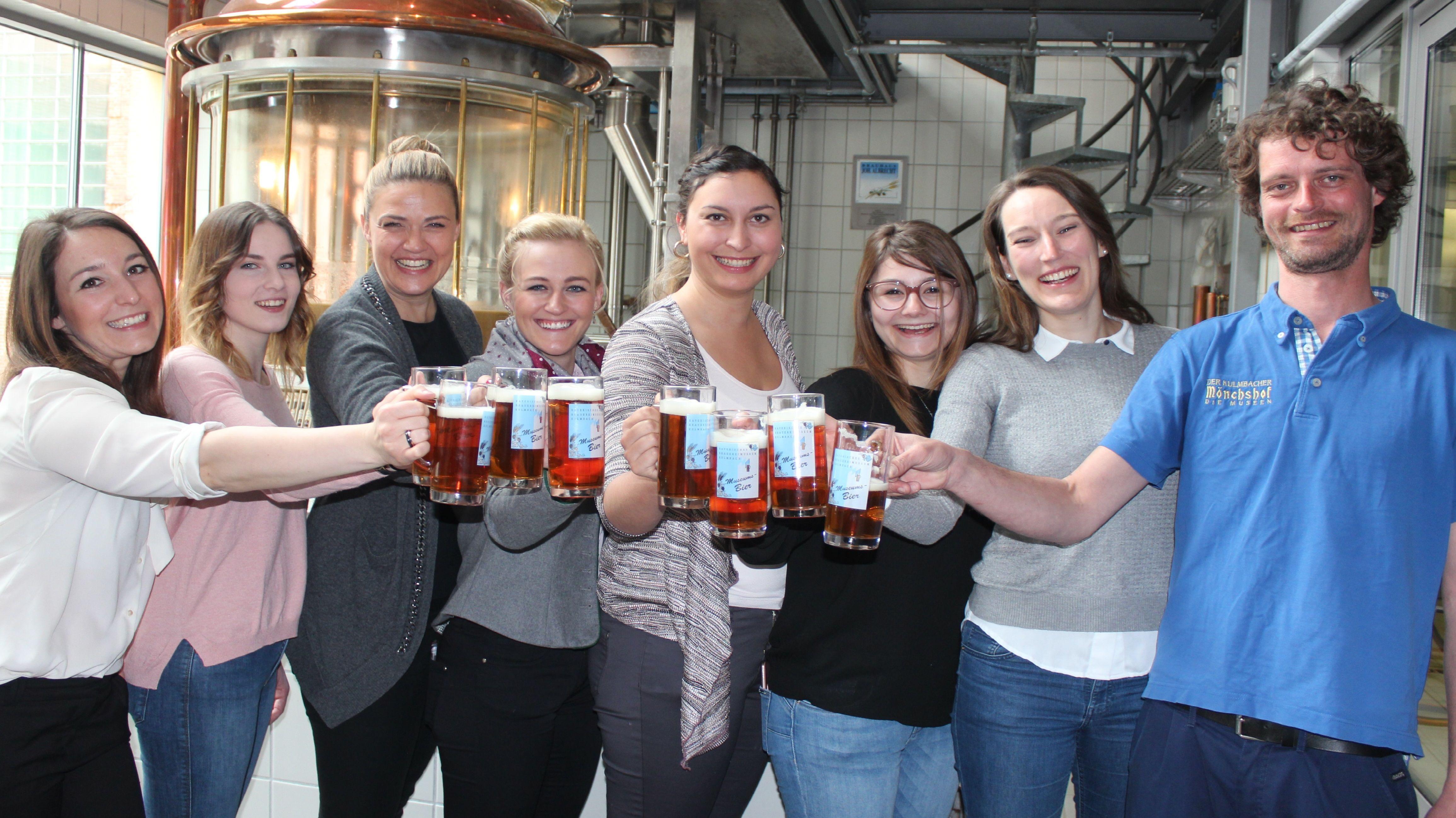Sieben Frauen mit einem Bierkrug in der Hand stoßen mit einem Braumeister an.