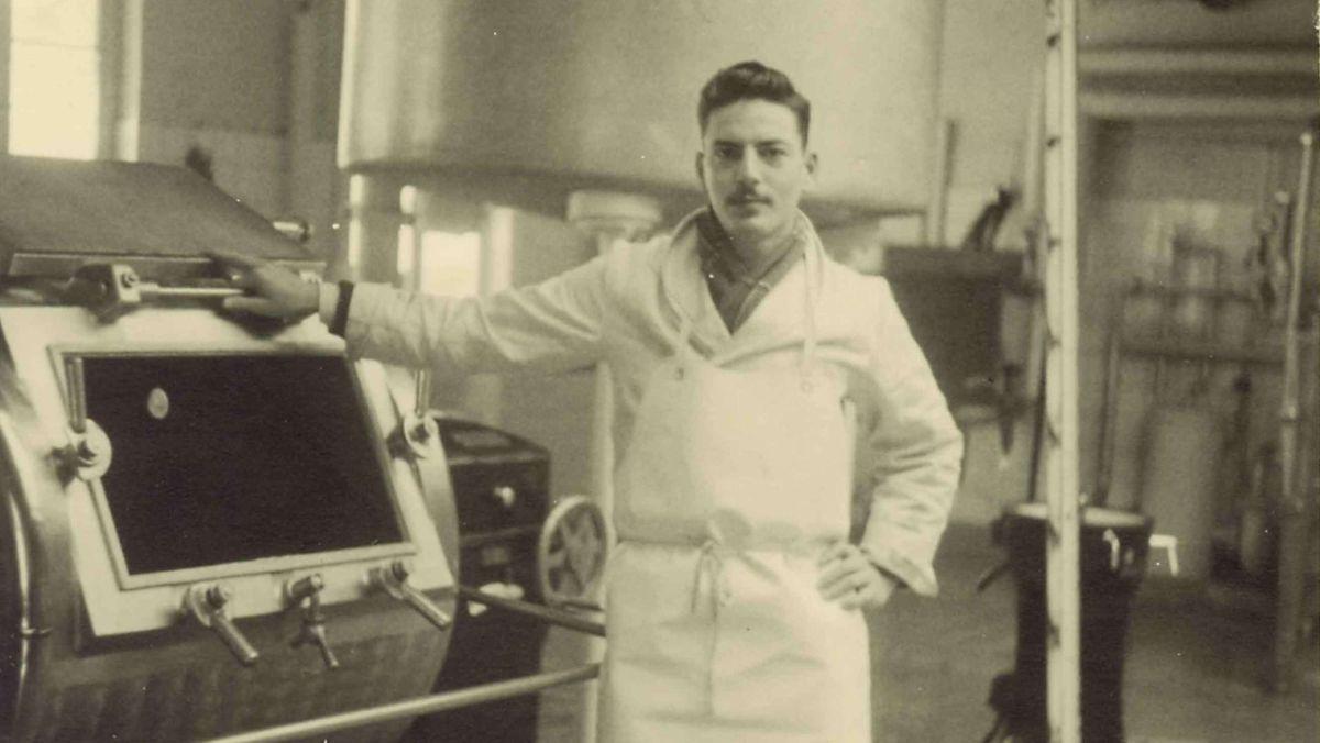 Schwarz-weiß Foto des jungen Michael Strauss vor einer Maschine in einer Fabrik des Unternehmnes.