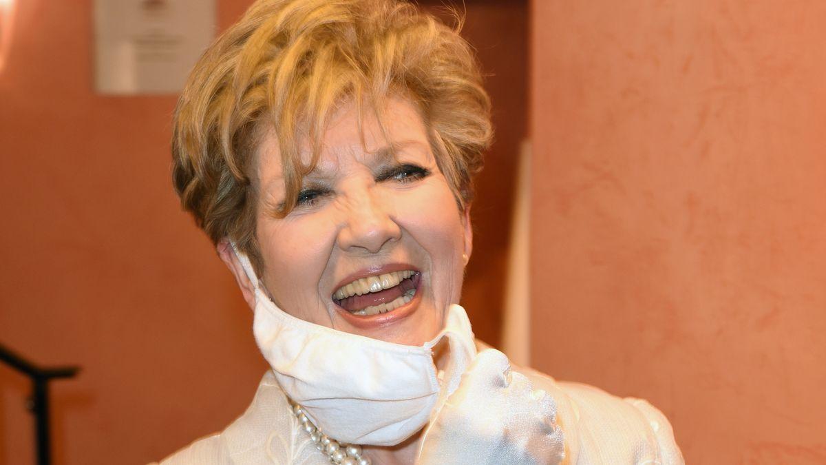 Porträt von Carolin Reiber, lächelnd und mit halb herunter gezogener Maske