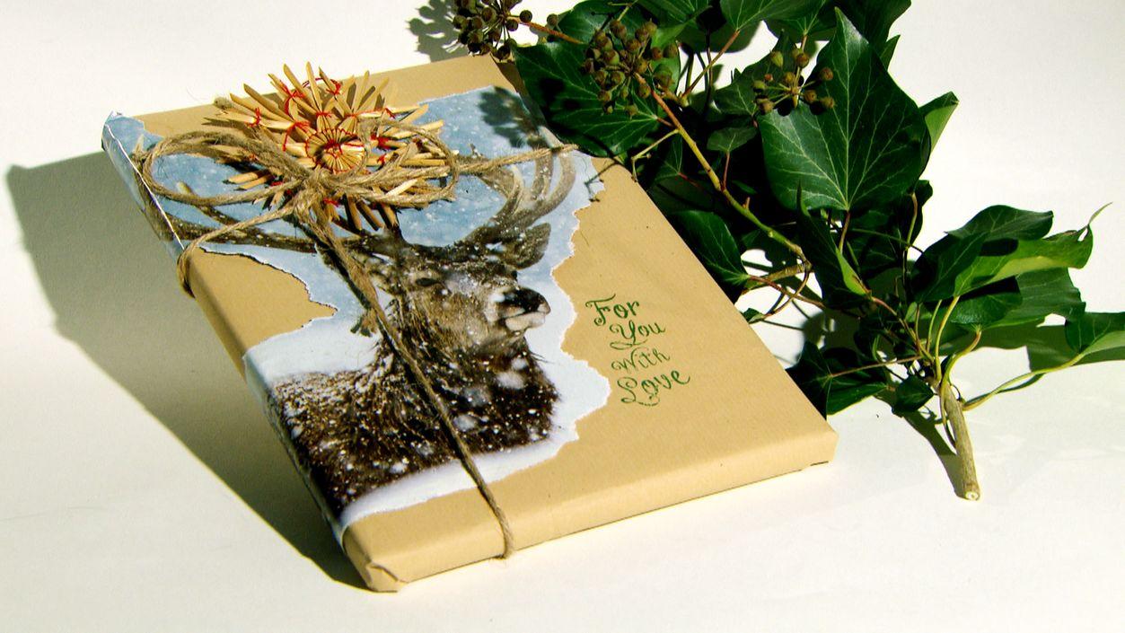 Buch in Packpapier mit Bindfaden und Zeitungsausschnitten dekoriert