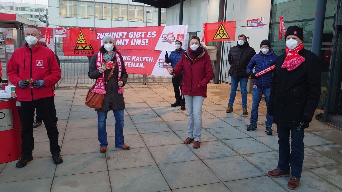 Im Morgenlicht stehen mehrere Mitglieder der Gewerkschaft IG Metall mit Abstand, Schutzmasken und teils auch mit Schals und Jacken mit IG-Metall-Logo vor dem Werkstor bei Audi in Ingolstadt.