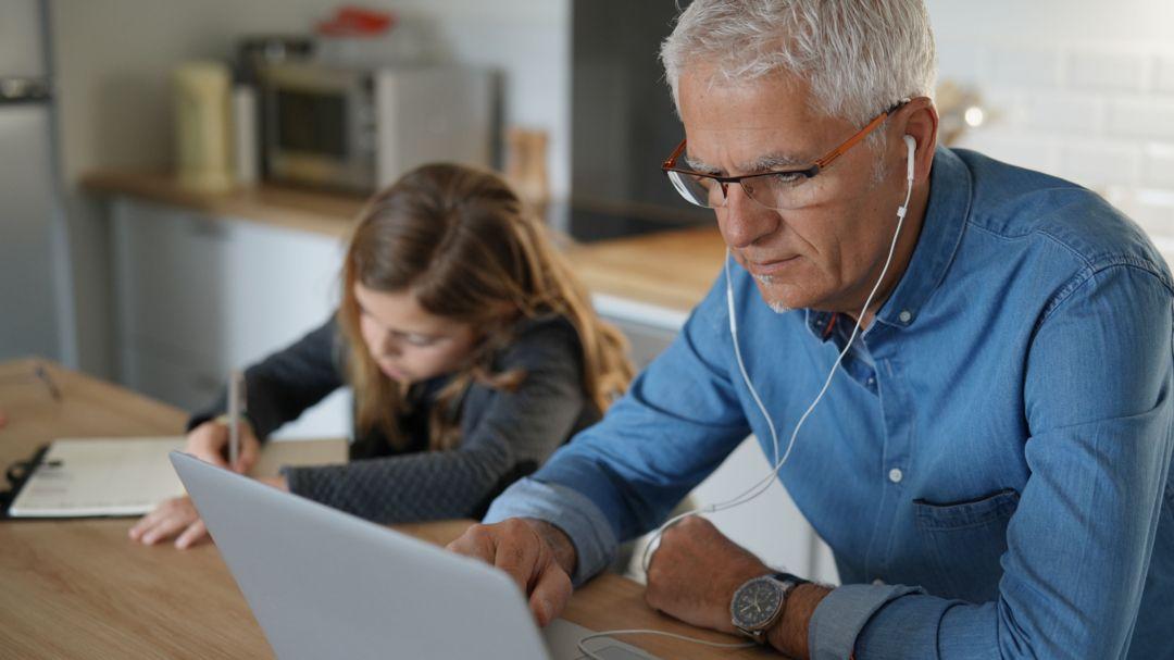 Ein Vater arbeitet in der Küche am Laptop mit Kopfhörern, neben ihm sitzt seine Tochter und macht Hausaufgaben.