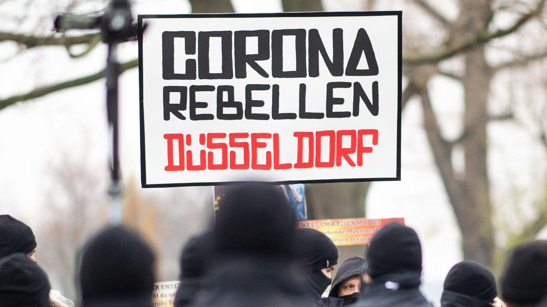 """Demonstranten halten im Dezember ein Schild mit der Aufschrift """"Corona Rebellen Düsseldorf"""" in die Höhe."""