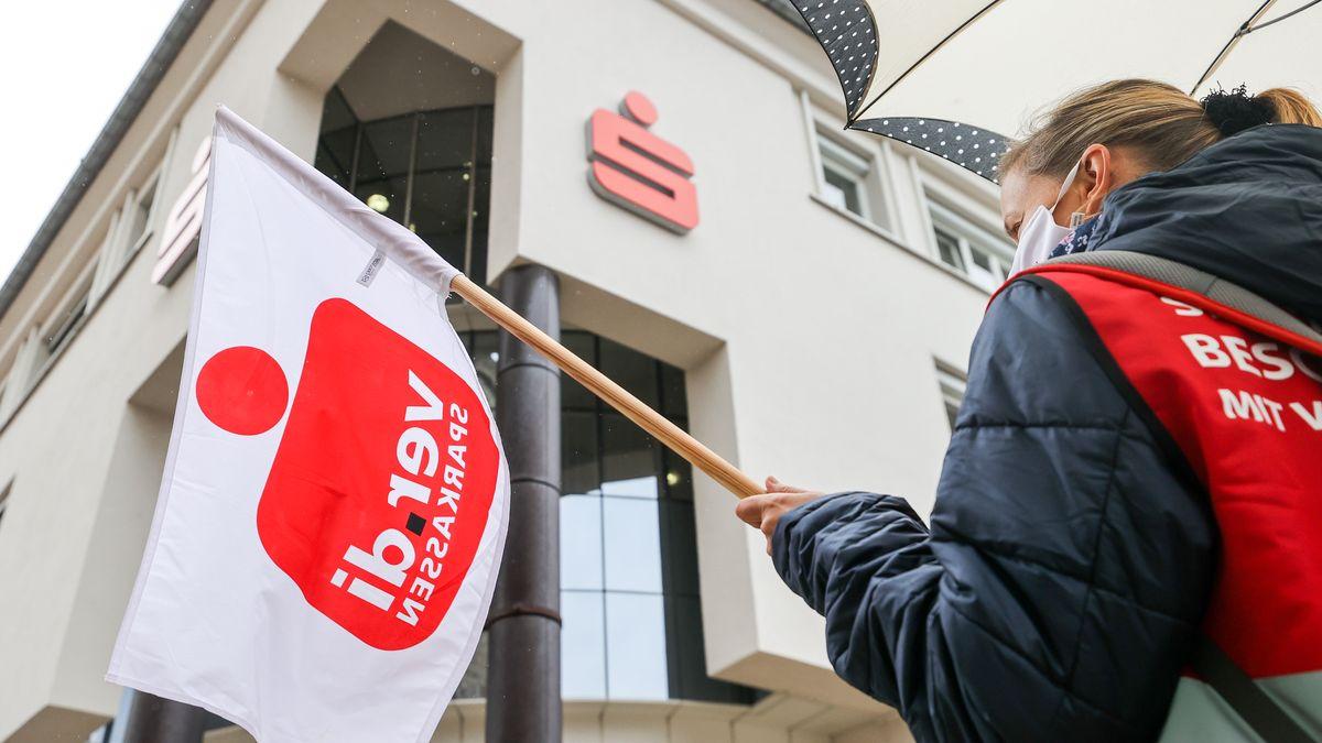 Eine Beschäftigte einer Sparkassen in Sachsen demonstriert Anfang Oktober mit einer Fahne in der Hand im Rahmen eines Warnstreiks.