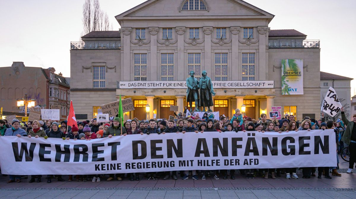 """Demo am Abend in Weimar (Thüringen): """"Wehret den Anfängen - Keine Regierung mit Hilfe der AFD"""" steht auf einem Transparent, das Demonstranten vor dem Theater und dem Goethe- und Schillerdenkmal halten. Die Menschen demonstrieren gegen den neuen Ministerpräsidenten von Thüringen."""