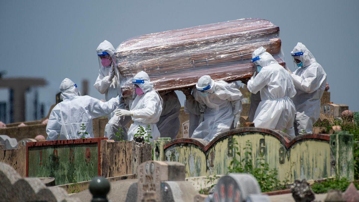 Malaysia, Selangor: Menschen in Schutzanzügen tragen einen Sarg eines Corona-Opfers auf einem Friedhof. Foto: Chong Voon Chung/XinHua/dpa +++ dpa-Bildfunk +++