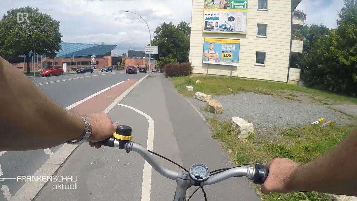 Ein Fahrradfahrer schaut auf den Radweg, der auf eine Straße einbiegt, dann aber nach wenigen Metern endet.