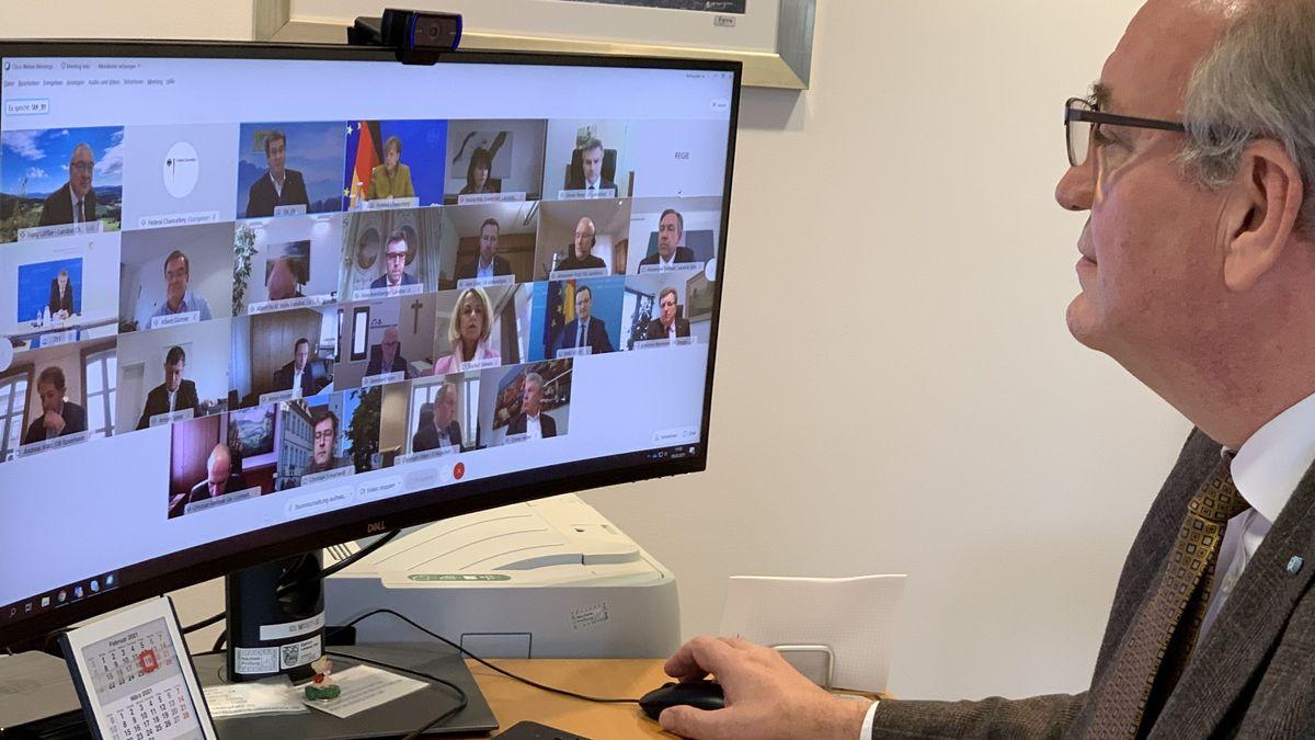 Ein Mann sitzt während einer Videokonferenz vor einem Bildschirm.