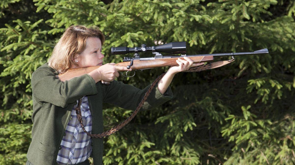Jägerin in Jagdkleidung mit Gewehr im Anschlag