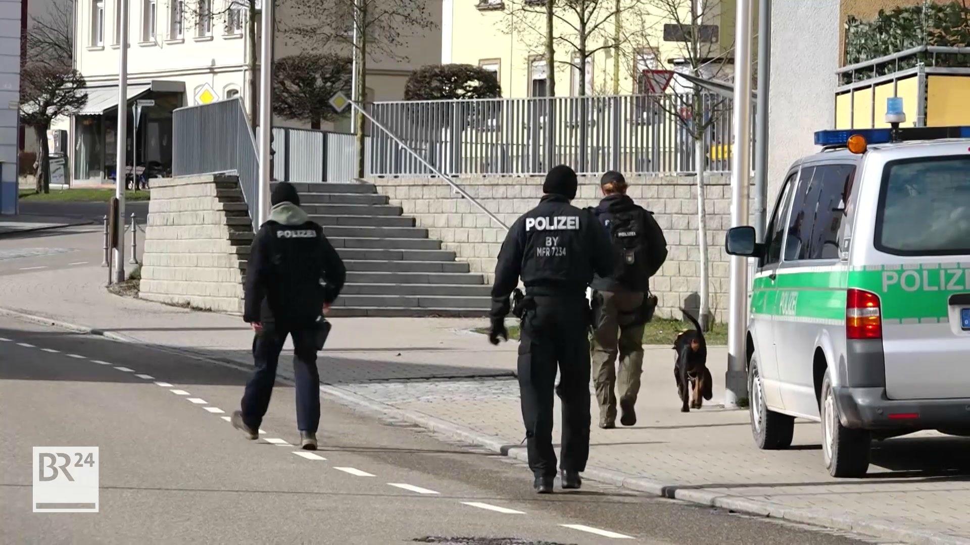 Zwei Bereitschaftspolizisten und ein Hundeführer laufen auf einer Straße