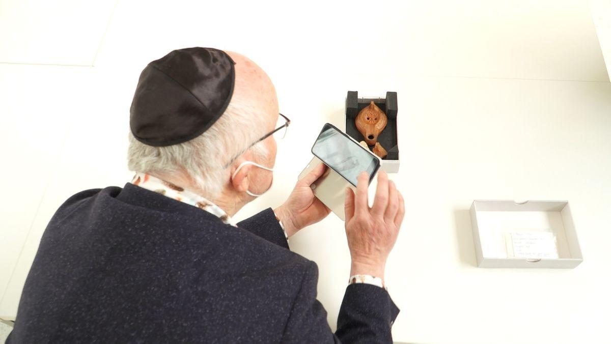 Josef Strzegowski von der jüdischen Gemeinde Augsburg fotografiert eine Tonscherbe mit Menorah-Abbildung