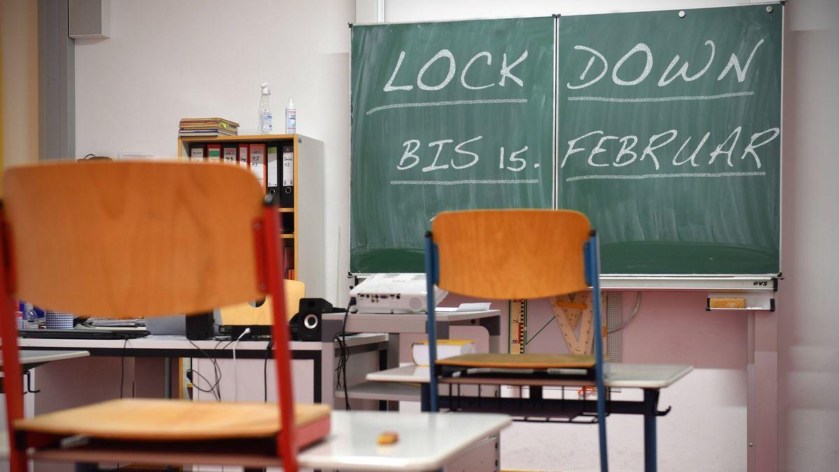 """Leeres Klassenzimmer, auf der Tafel steht """"Lockdown bis 15. Februar""""."""