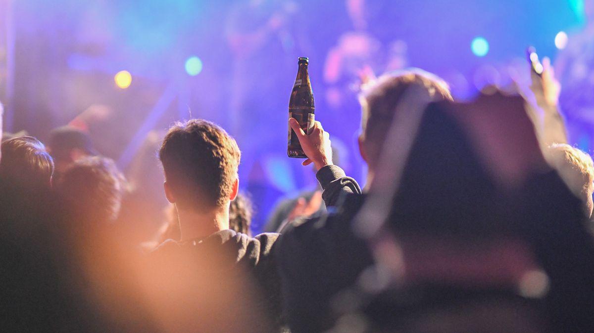 Nachtclub, Mann mit Bierflasche in der Hand hebt Arm, bunte Lichter