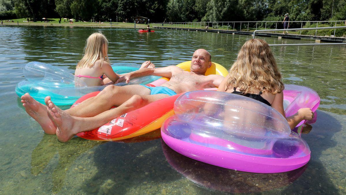 Ein Vater und seine Töchter sind bei sommerlichen Temperaturen mit Luftmatratzen im Badesee unterwegs.
