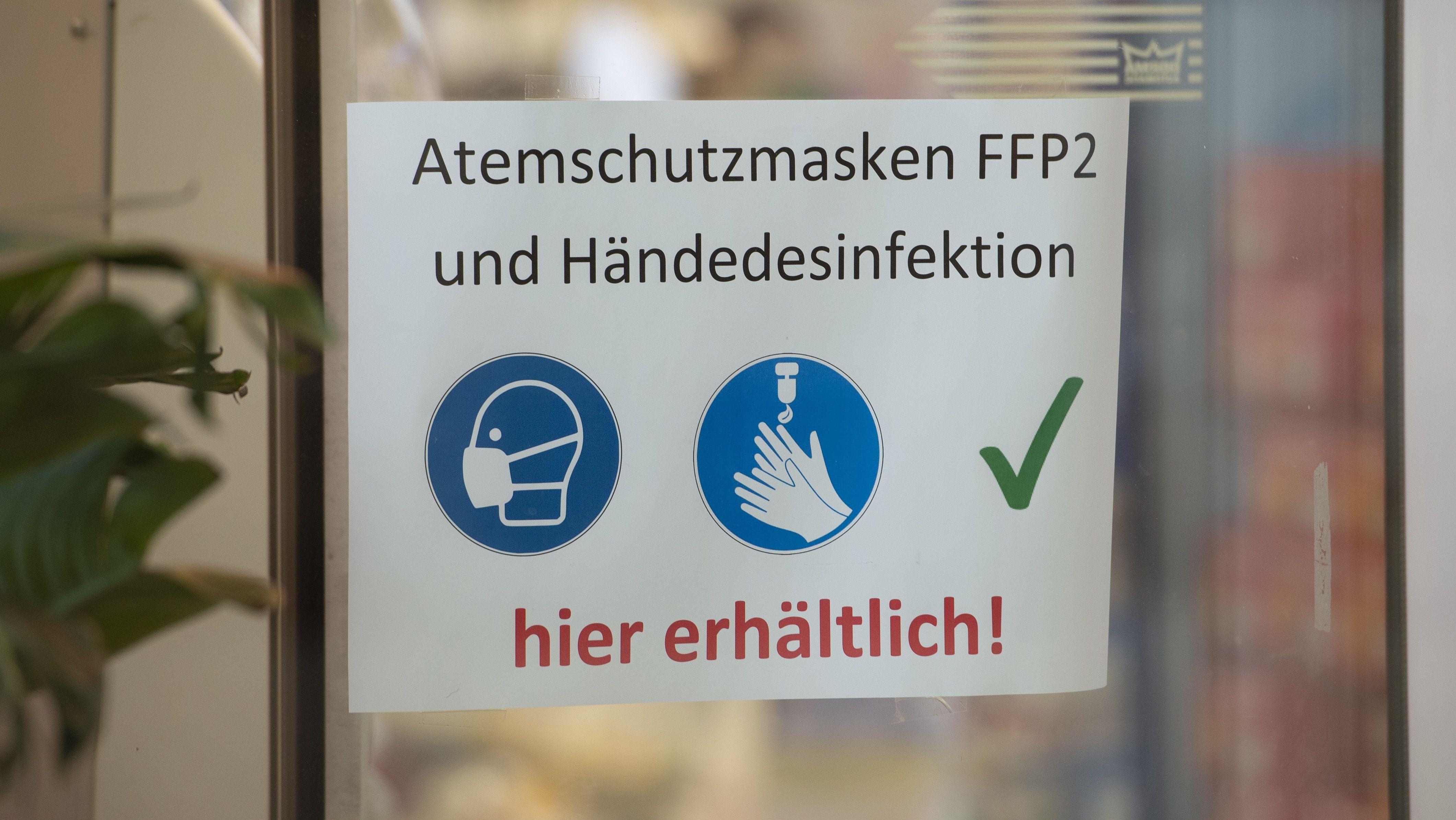 Schild am Fenster einer Apotheke: Atemschutzmasken FFP2 und Händedesinfektion hier erhältlich