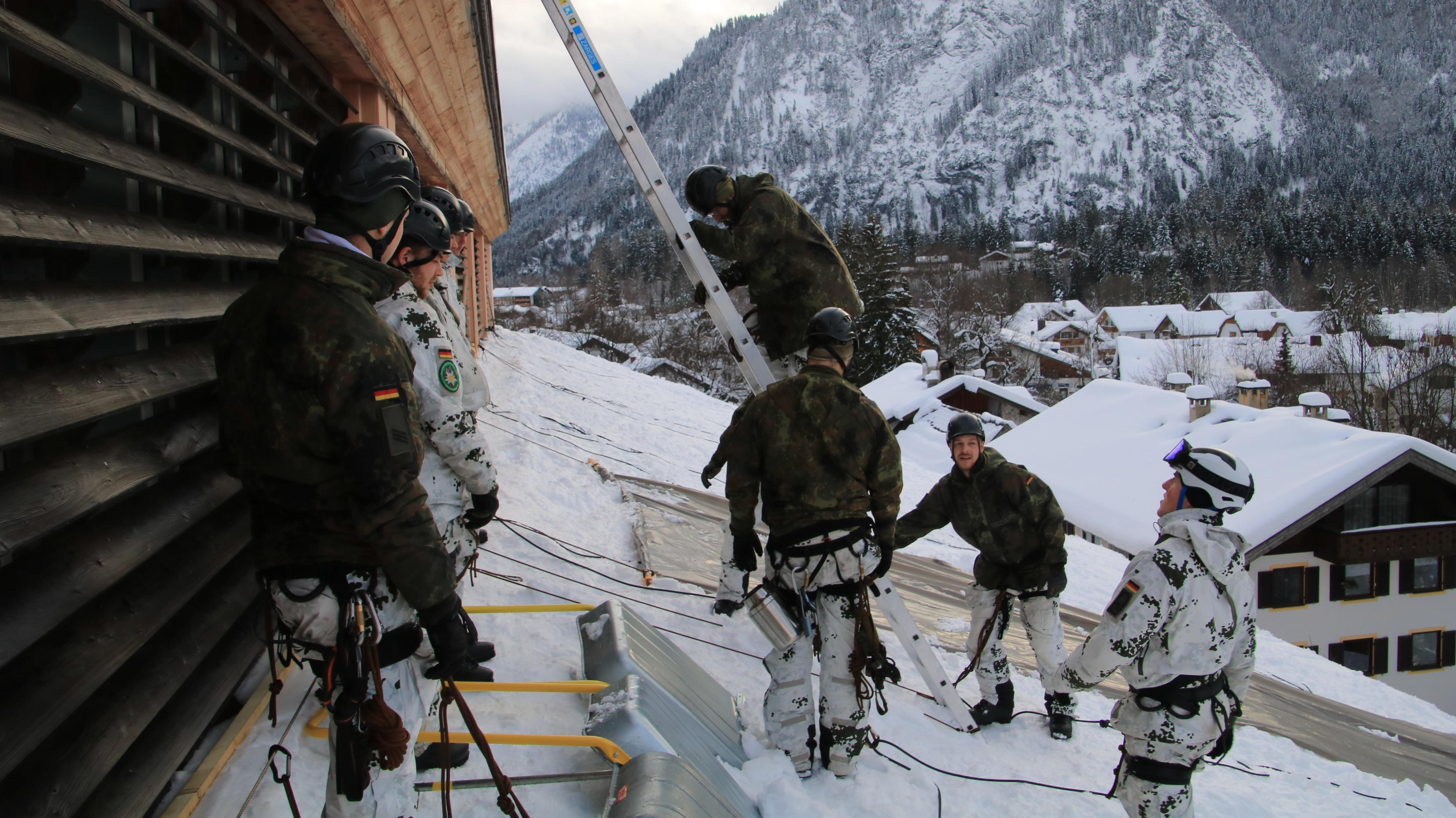 Gebirgsjäger kämpfen mit den Schneemassen auch auf dem Dach des Passionstheaters in Oberammergau.