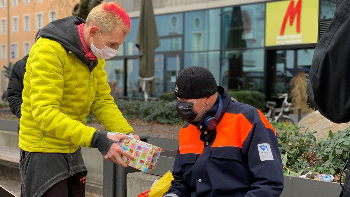 Caritas Streetworker Ben Peter übergibt Geschenk an 50-Jährigen Patrick aus Regensburg