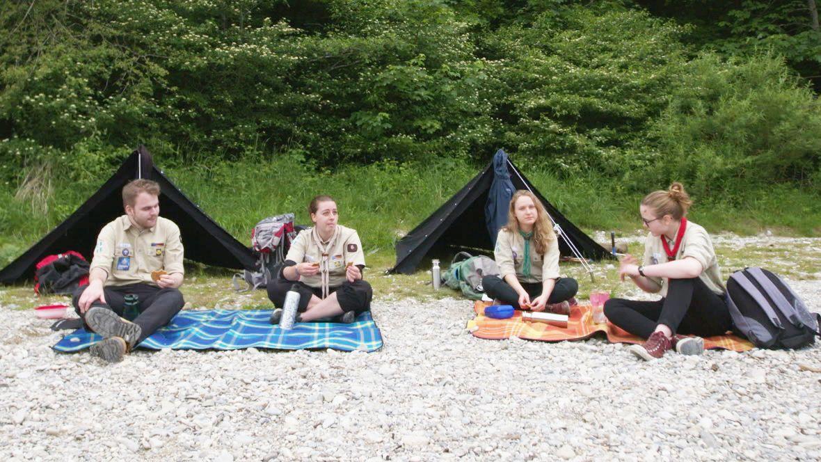 Pfadfinder der katholischen Deutschen Pfadfinderschaft Sankt Georg sitzen vor ihren Zelten am Flußufer