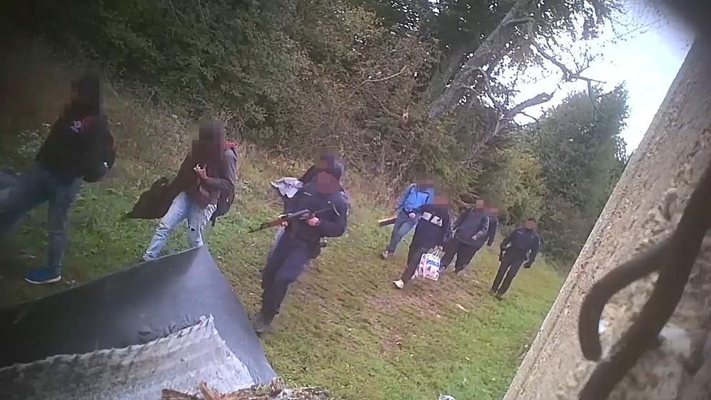 Herbst 2018, im Nordwesten des kroatisch-bosnischen Grenzgebiets: Eine Gruppe von Menschen wird von bewaffneten kroatischen Polizisten in Richtung des nahegelegenen bosnischen Staatsgebiets geführt.  | Bild:Border Violence, Nichtregierungsorganisation