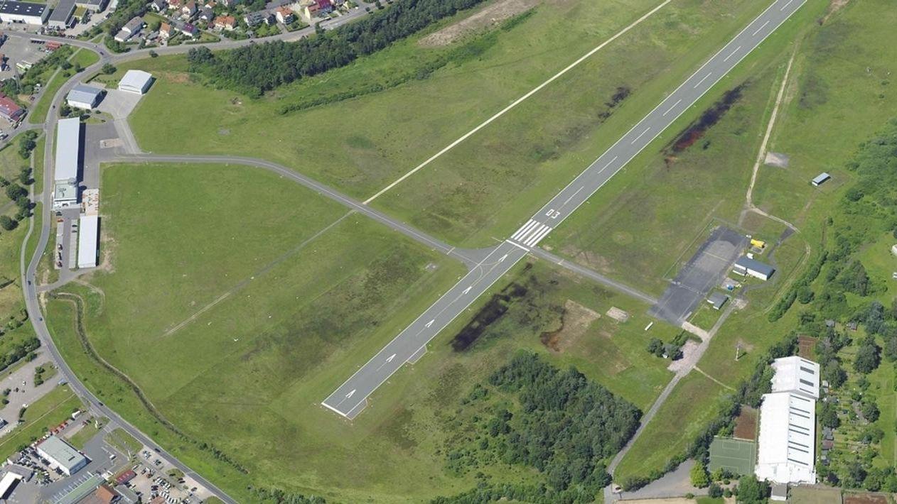 Eine graue Landebahn aus der Vogelperspektive, umrahmt von Wiesenflächen und Gebäuden