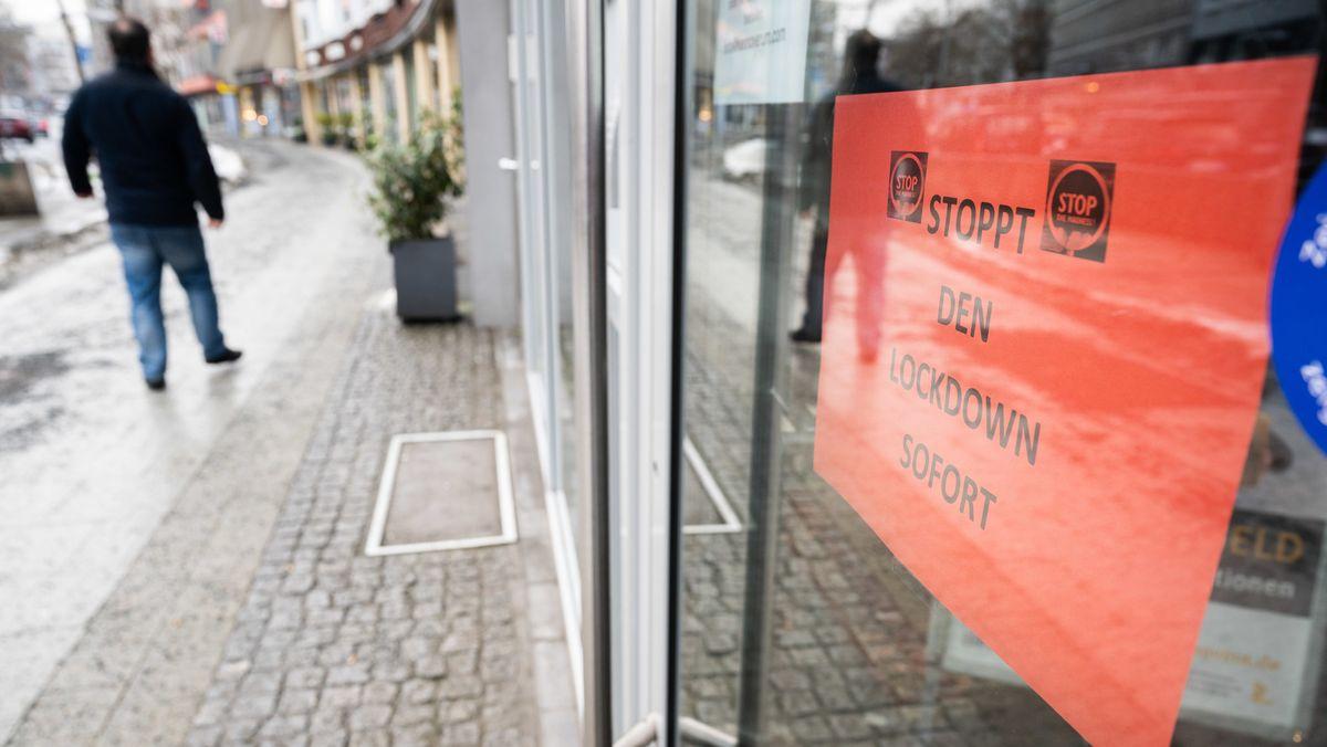 """Ein Schild """"Stoppt den Lockdown sofort"""" hängt in der Eingangstür eines Geschäfts."""