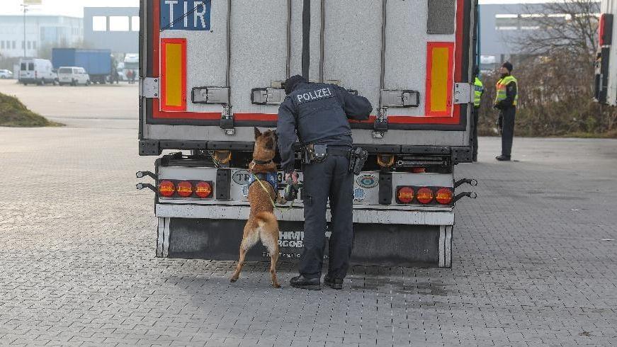 Ein Bundespolizist und ein Suchhund an einem Lkw