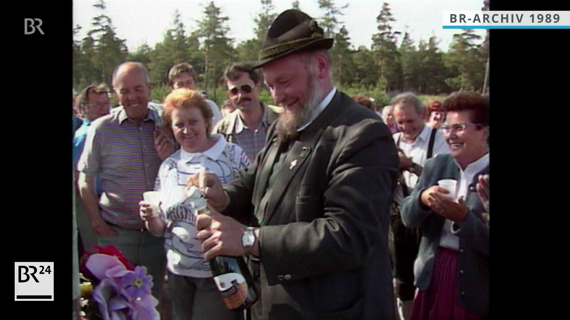 Pfarrer Salzl beim Öffnen einer Sektflasche