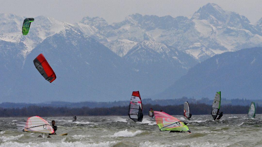 Bayern, Herrsching: Windsurfer und Kiter nutzen den starken Wind auf dem Ammersee, vor der Kulisse der noch verschneiten Berge.