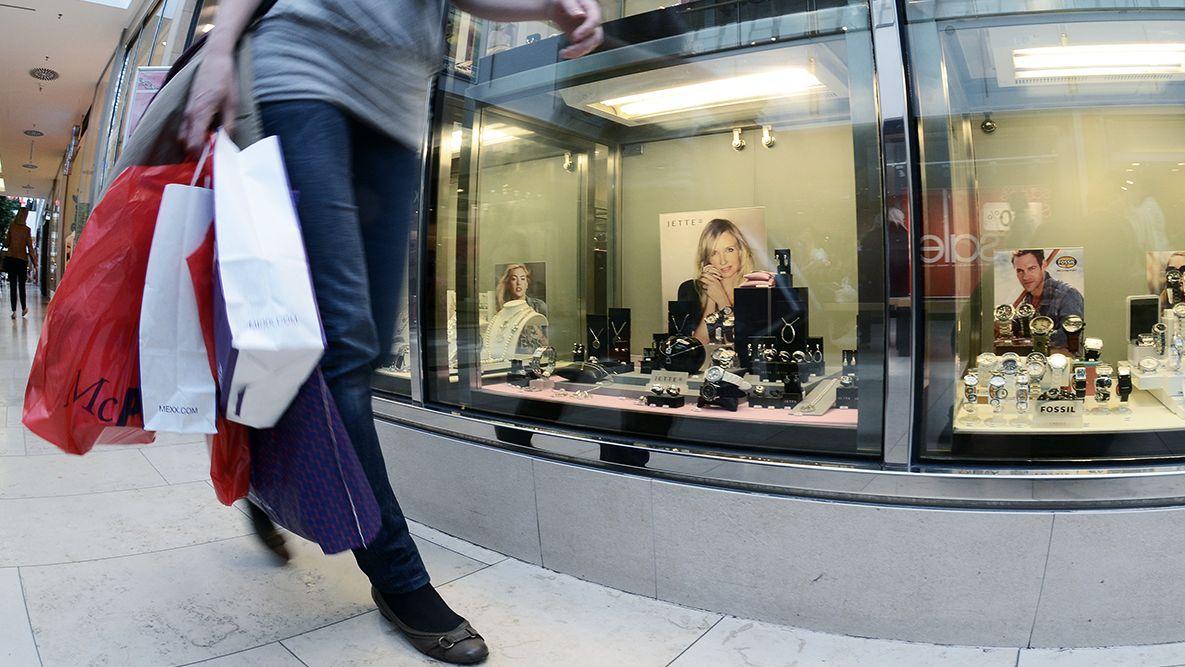 Eine Frau läuft mit Einkaufstaschen an einem Schaufenster in einem Einkaufszentrum vorbei.