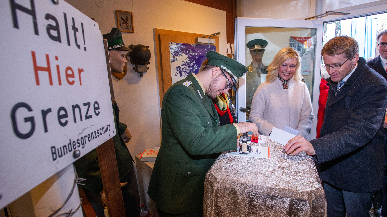 Manuela Schwesig (SPD), die Ministerpräsidentin von Mecklenburg-Vorpommern und Daniel Günther (CDU, r), Ministerpräsident von Schleswig-Holstein erhalten im Grenzmuseum in der Nähe des früheren Grenzübergangs Schlutup beim der Feier zur Erinnerung an den Mauerfall vor 30 Jahren von einem Bundesgrenzschützer den Ausreisestempel in die DDR.