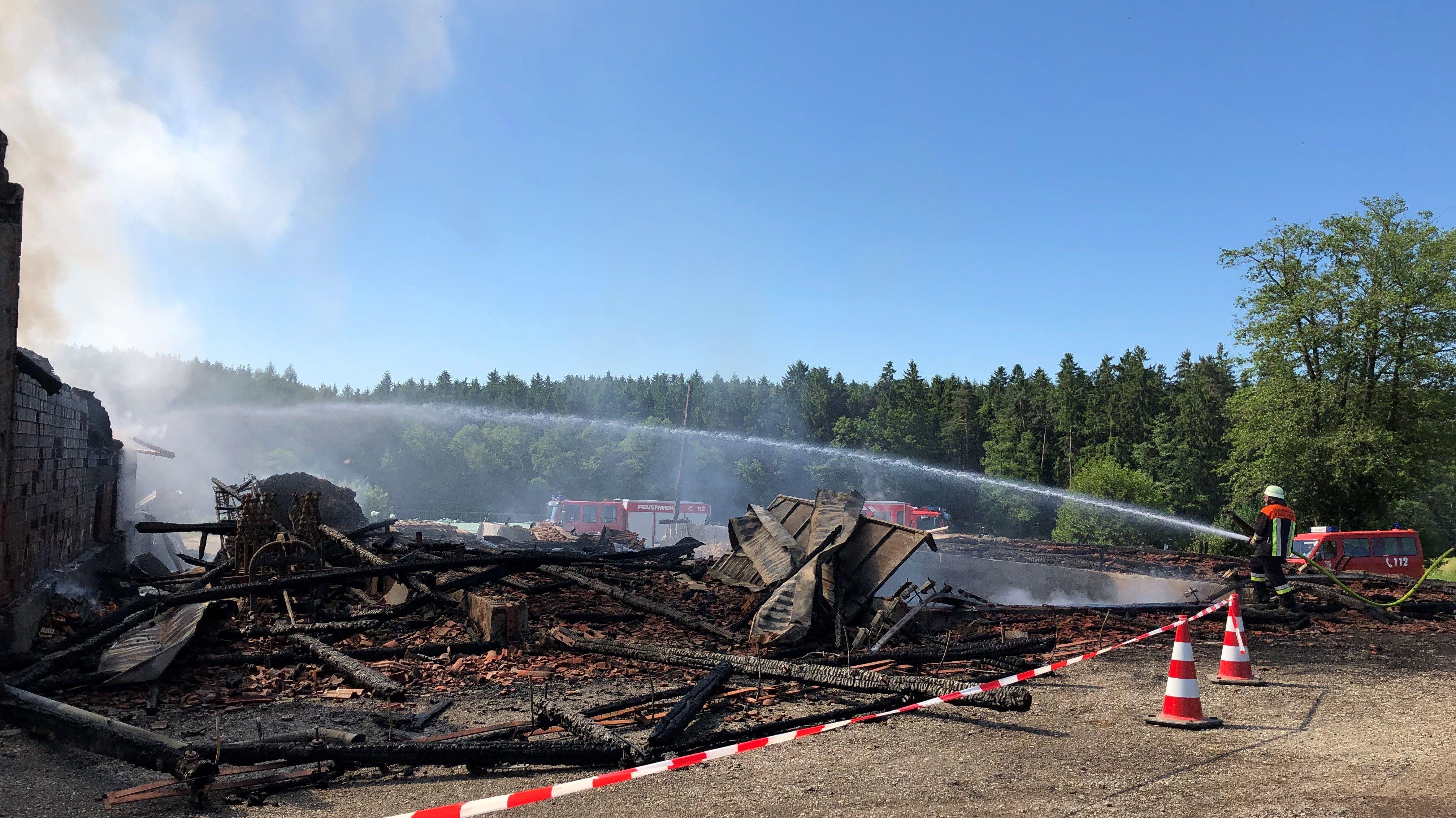 Ein Feuerwehrmann löscht den Brand auf einem Bauernhof in Malgersdorf.