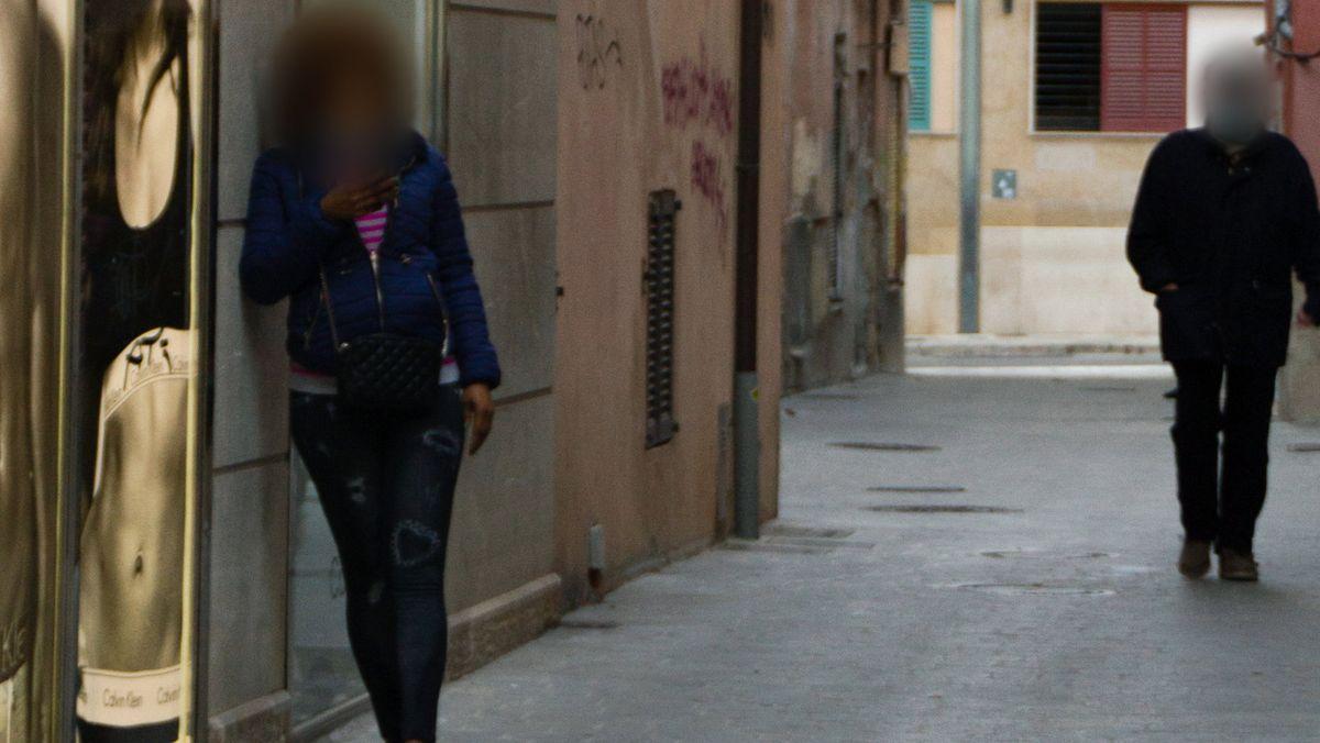 Eine Frau lehnt sich an ein Haus und wartet an der Puerta de Sant Antoni in Palma de Mallorca auf Kunden. Rechts läuft eine weitere Person.