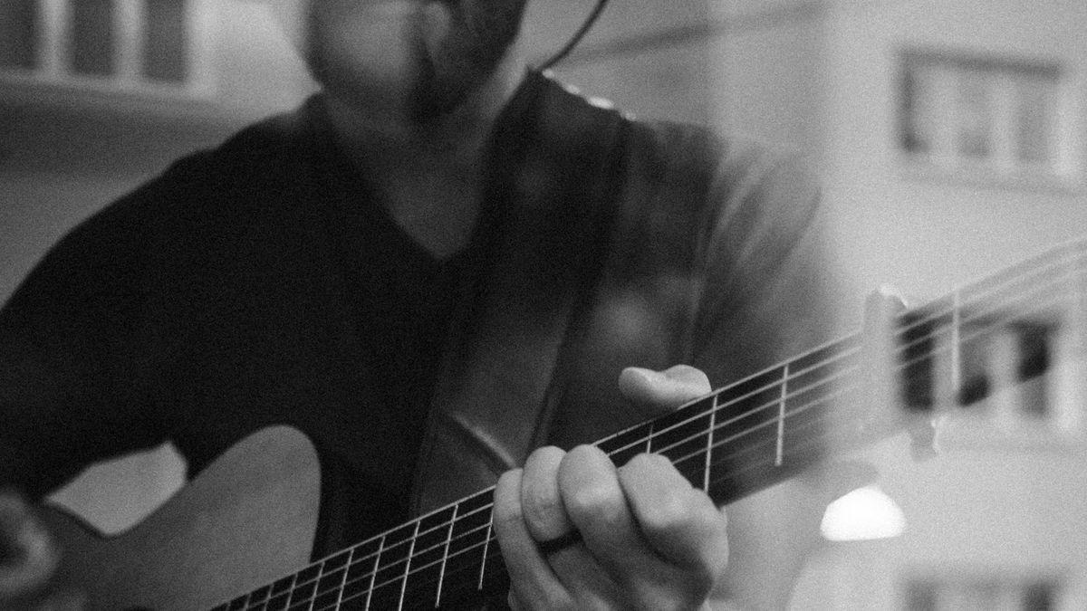 Ein Mann spielt auf einer Gitarre, er hat ein Headset auf.