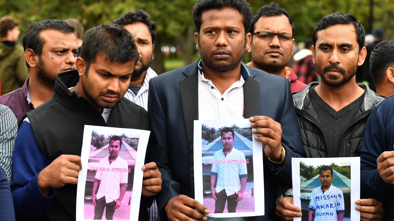 Eine Gruppe muslimischer Männer zeigt das Foto eines Freundes, der mutmaßlich bei dem Anschlag ums Leben gekommen ist.