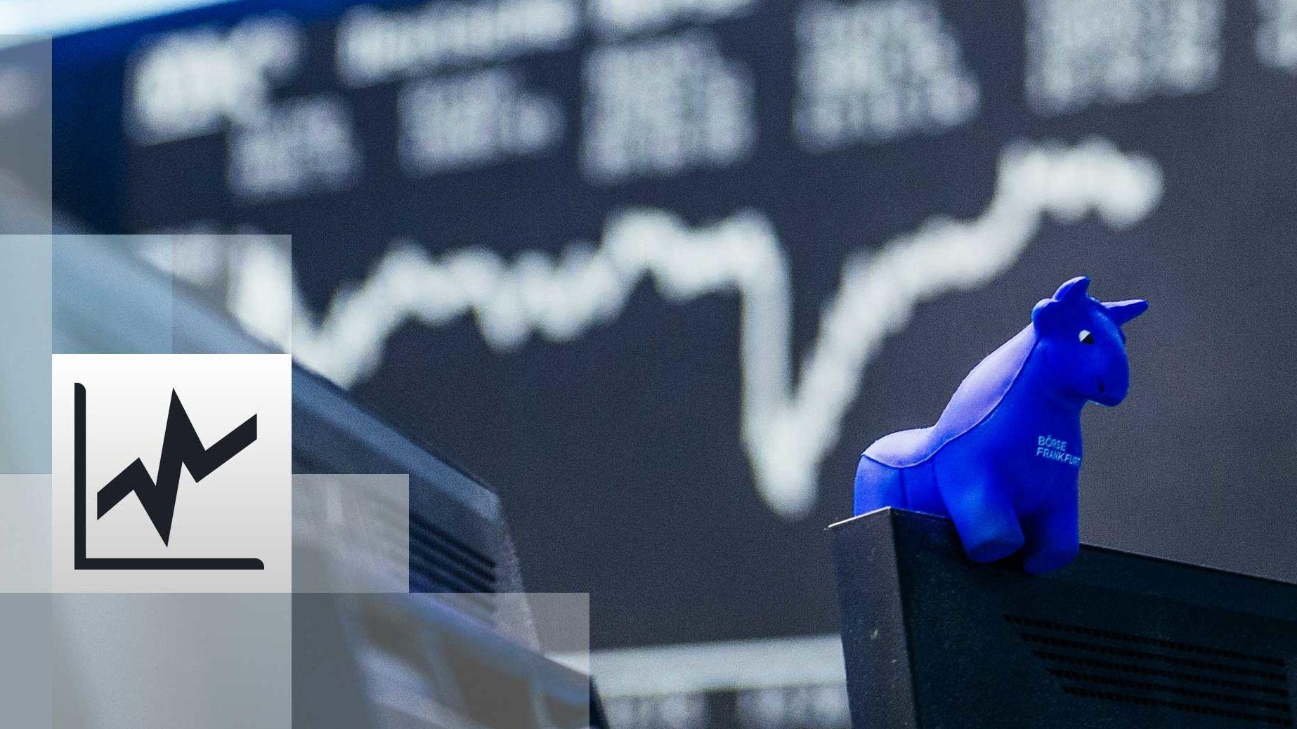 : ein blauer Stier aus Gummi sitzt auf der oberen Kante eines Bildschirmes, im Hintergrund die Kurstafel der Börse
