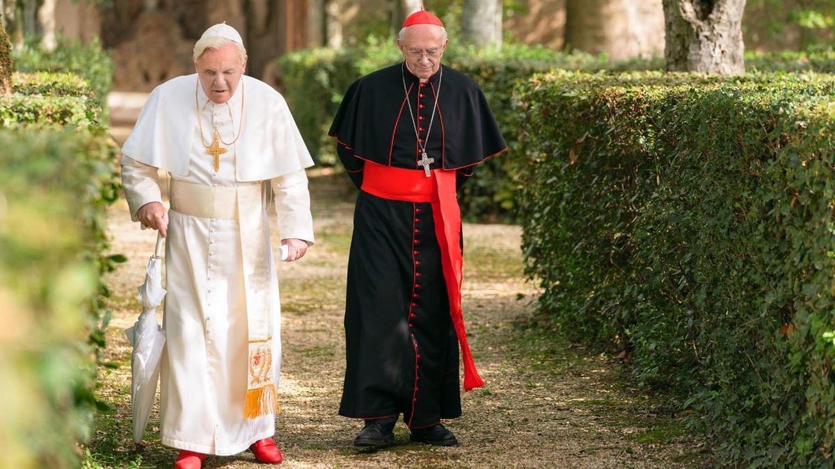 """Filmszene: Anthony Hopkins und Jonathan Pryce wandeln als """"Die zwei Päpste"""" durch eine heckengesäumte Gartenanlage"""