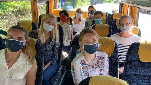 Medizinstudierende, die alle einen Mundschutz tragen, sitzen in einem Bus.