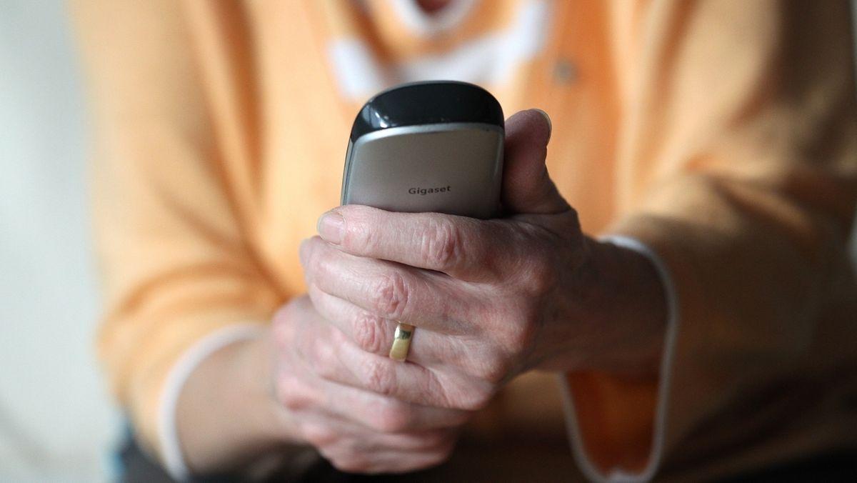 Eine Seniorin hält ein mobiles Telefon in der Hand.